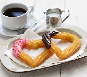 זוג מאפים מצופים בצורת לב לצד כוס קפה עם חלב