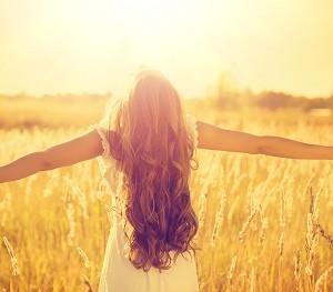 אישה פורסת ידיה בטבע ומביטה מעלה