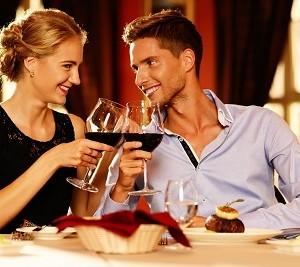 זוג צעיר מרים כוסית יין במסעדה