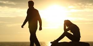 אישה יושבת על סלע ומחזיקה את ראשה בידיה, ובן זוגה מתרחק ממנה