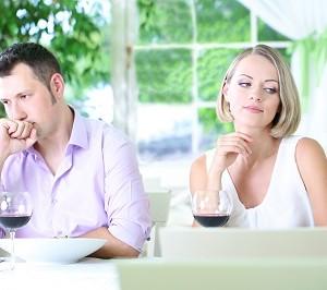 בני זוג יושבים במסעדה ולא מביטים זה על זה.