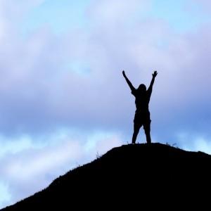 קווי מתאר של אישה עומדת על גבעה ומרימה ידיה לשמים