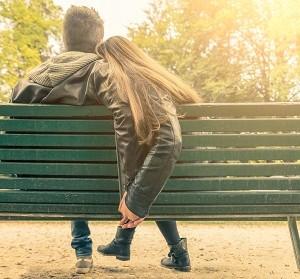 גבר ואישה יושבים על ספסל ואוחזים ידיים