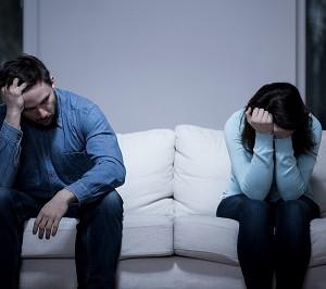 גבר ואישה יושבים מרוחקים ומיואשים על ספה