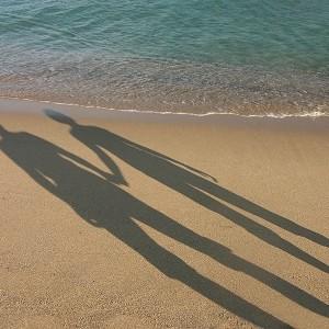 צללים של גבר ואישה אוחזים ידיים על חוף הים