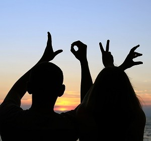 זוג אוהבים יוצר את המילה LOVE באמצעות ידיהם