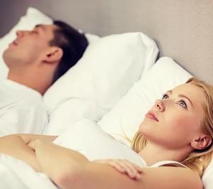 אישה שוכבת טרודה במיטתה בעוד בן זוגה ישן לצידה